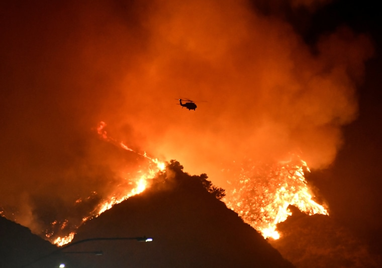 Image: A firefighting helicopter flies over the Getty Fire as it burns in the hills west of the 405 freeway in the hills of West Los Angeles, California