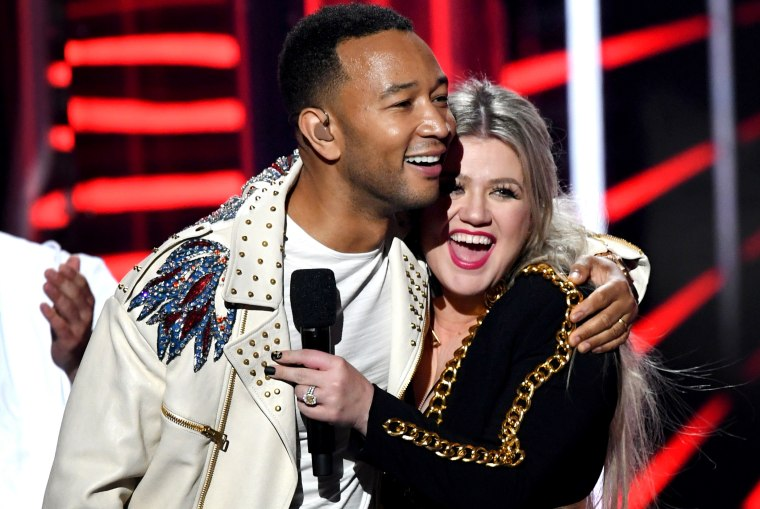 Image: John Legend and Kelly Clarkson embrace at the Billboard Music Awards in Las Vegas in 2018.