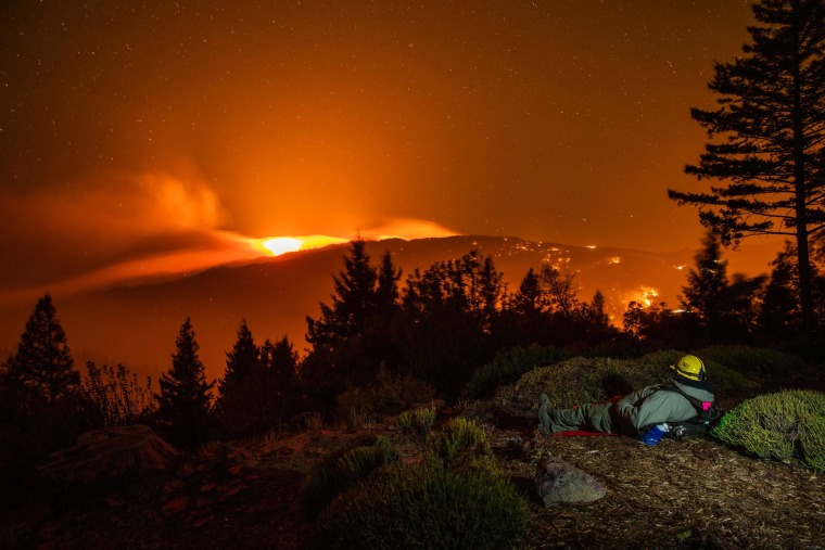 Image: Alex DeLeon with Engine 342 of the Lake Tahoe Basin Management Unit of the U.S. Forest Service watches the Kincade fire burn on a ridge between Lake and Sonoma Counties, as he stands watch at a home above Knights Valley east of Healdsbur