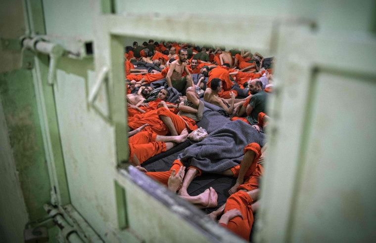 Image: Men suspected of being affiliated with the Islamic State (IS) group, gather in a prison cell in the northeastern Syrian city of Hasakeh