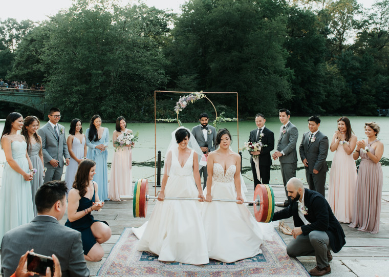 Zeena Hernandez, left, and Lisa Yang, deadlift a 253 pound barbell during their wedding ceremony in Prospect Park