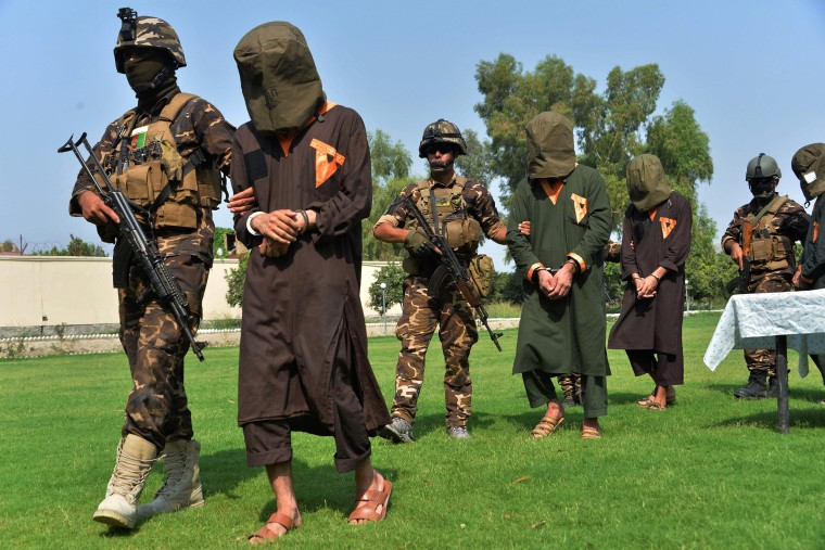 Image: Afghan security personnel escort arrested alleged Taliban and Islamic State militants during an operation in Jalalabad province