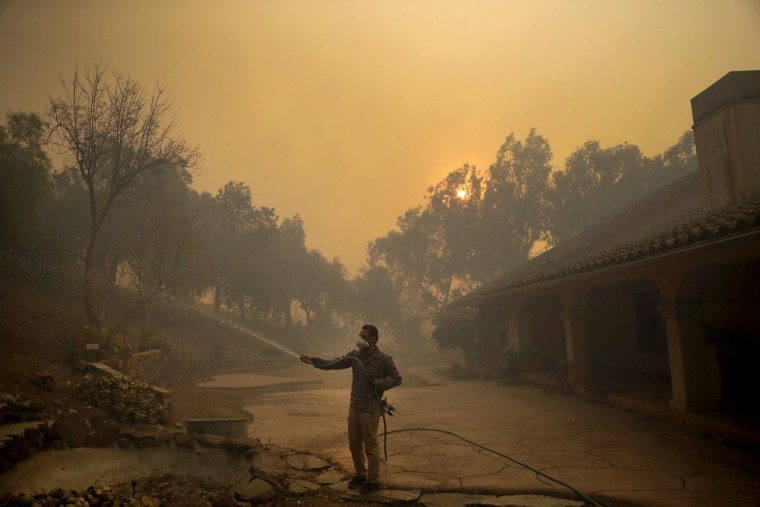 Image: Marco Alcaraz hoses down his girlfriend's house as the Easy fire approaches in Simi Valley, Calif., on Oct. 30, 2019.