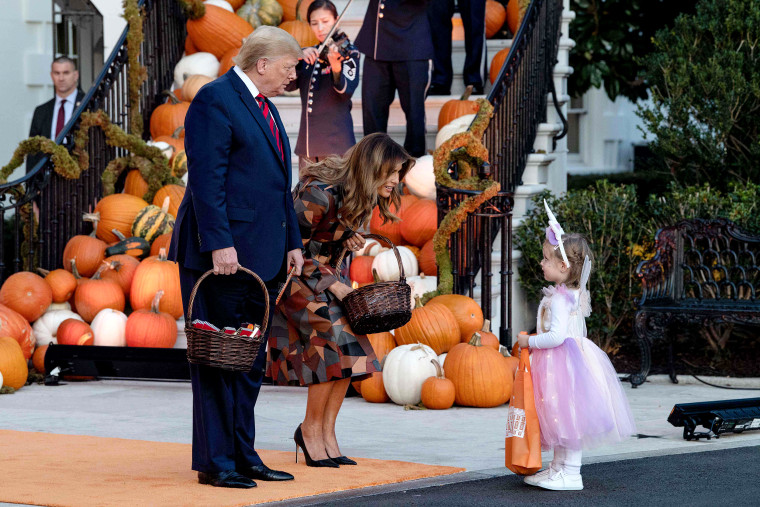 Image: President Trump and the first lady hand out Halloween candy to a little girl at the White House