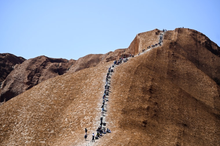 Image: Tourists climb Uluru, formerly known as Ayers Rock, at Uluru-Kata Tjuta National Park in the Northern Territory