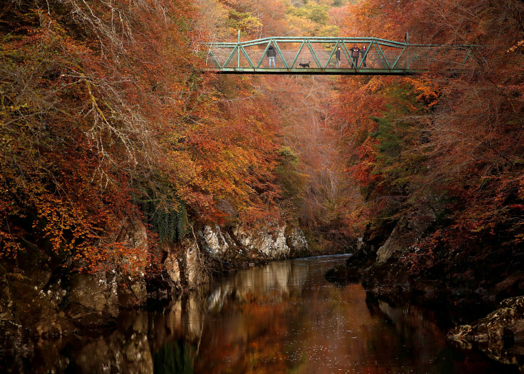 Image: People walk on the bridge over the river Garry, Pitlochry, Scotland