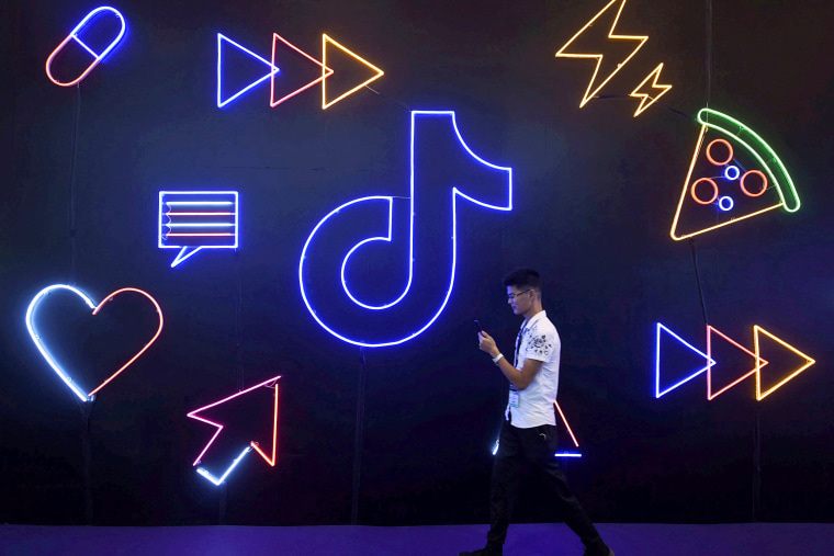 Image: FILE PHOTO: Man walks past a sign of ByteDance's app TikTok, known locally as Douyin, at an expo in Hangzhou