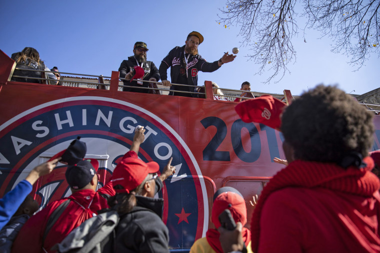 Washington Nationals Sean Doolittle pitcher tosses back a baseball after signing it for a fan before the victory parade in downtown Washington on Nov. 2, 2019.