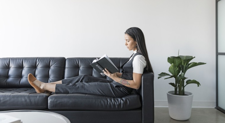 Woman reading book on leather sofa