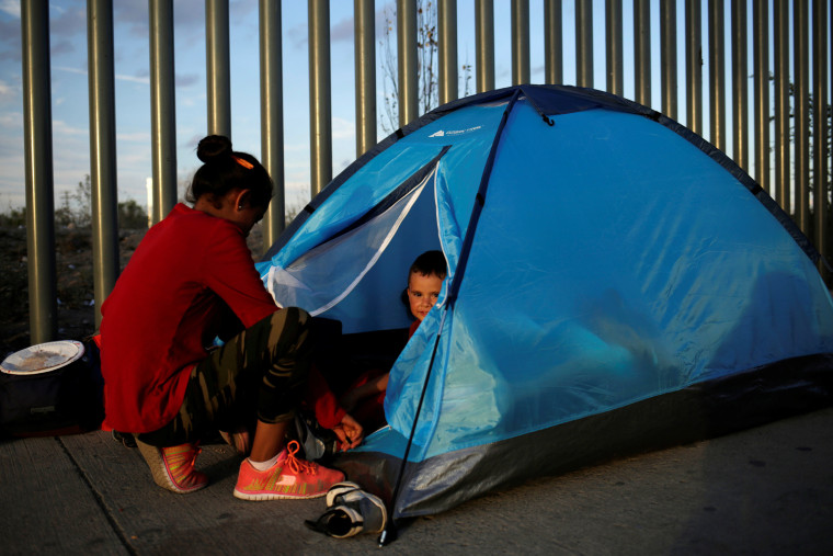 Image: A Mexican citizen fleeing violence camps in a queue with a child to try to cross into the U.S. to apply for asylum at Cordova-Americas border crossing bridge in Ciudad Juarez