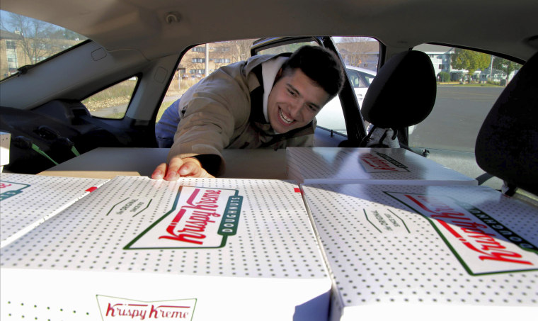 Jayson Gonzalez reaches into his car for another box of Krispy Kreme doughnuts for customers in Little Canada, Minn, who ordered online on Oct. 26, 2019. Gonzalez, a Minnesota college student, says Krispy Kreme has told him to stop making doughnut runs to Iowa. Gonzalez told the Pioneer Press he was told his sales created a liability for the North Carolina-based company.