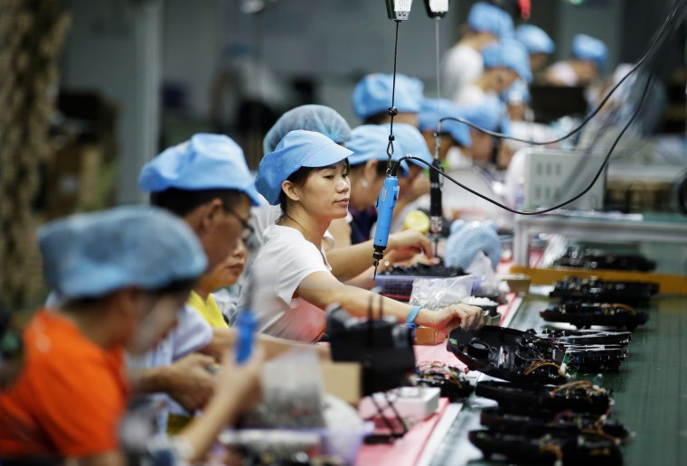 Employees work on the production line of a robot vacuum cleaner at a factory of Matsutek in Shenzhen