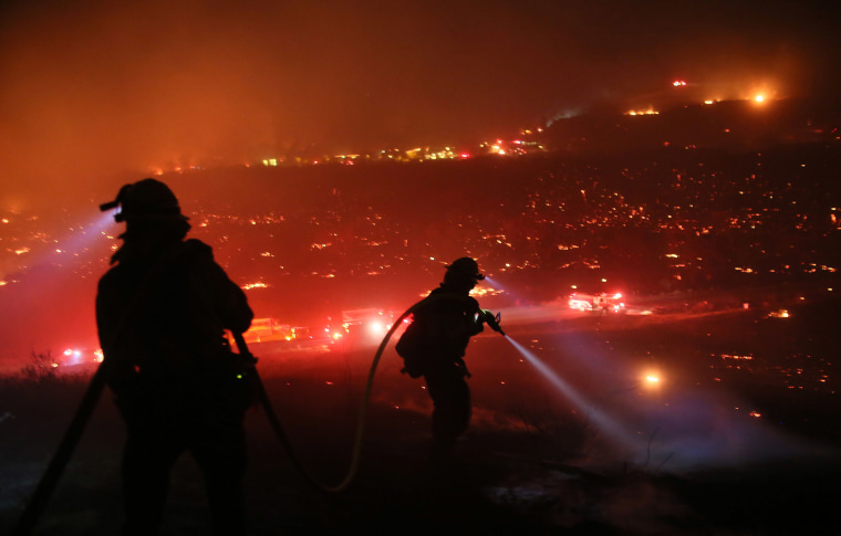 Image: Firefighters walk to the fire line at the Lilac fire in Bonsall, California.