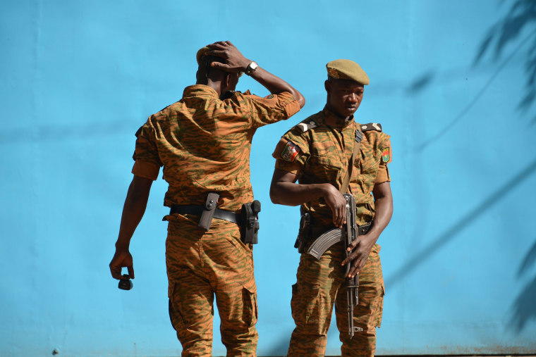 Image: Burkinabe men patrol the army's headquarters from the roof in Ouagadougou, Burkina Faso.