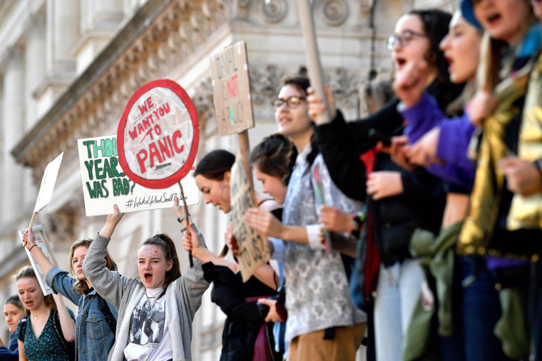 "Image: Young demonstrators hold placards as they attend a climate change protest organised by ""Youth Strike 4 Climate"", on Whitehall in central London"