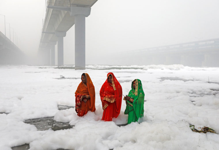 Image: Hindu women worship the Sun god in the polluted waters of the river Yamuna during the Hindu religious festival of Chatth Puja in New Delhi