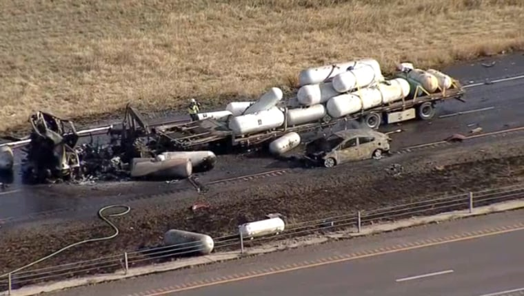 The site of a crash involving a flatbed truck carrying butane tanks and at least one other vehicle near Denton, Texas