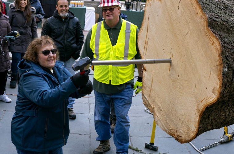 Image: Carol Schultz, who donated this year's tree, pounds a spike into the trunk at Rockefeller Center on Nov. 9, 2019.