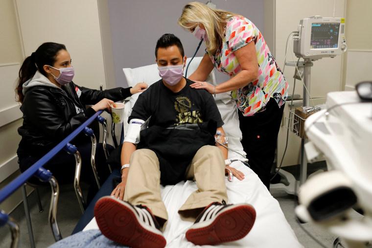 Image: Emergency room nurse Christine Bauer treats Joshua Lagade of Vista, California, for the flu as his girlfriend Mayra Mora looks on in the emergency room at Palomar Medical Center in Escondido, California, on Jan. 18, 2018.