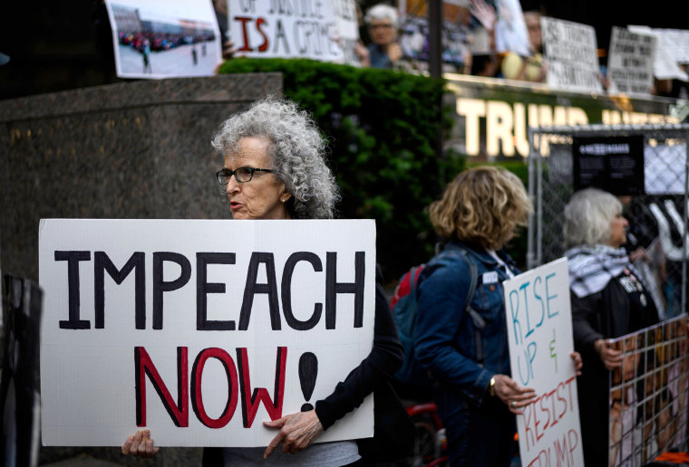 "A demonstrator with a sign reading ""Impeach now"" takes part in Trumps Birthday Protest in front of the Trump International Tower, June 14, 2019 in New York."