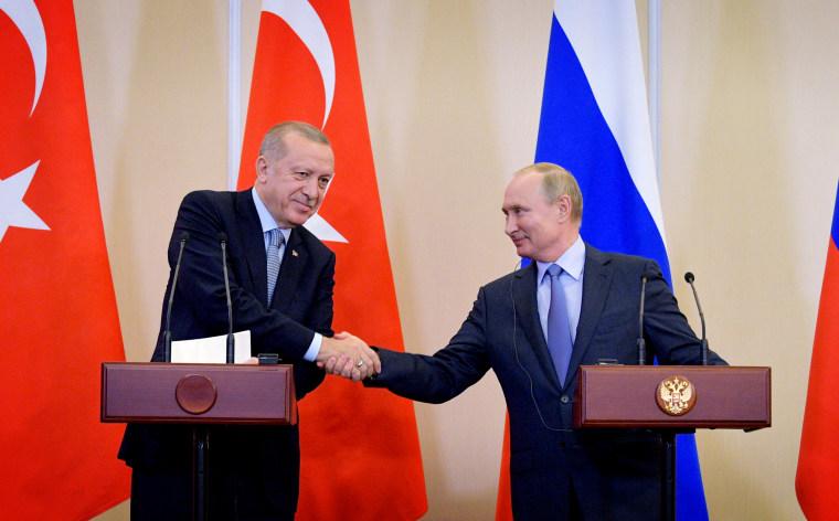 Image: Turkish President Tayyip Erdogan and Russian President Vladimir Putin shake hands following talks in Sochi on Oct. 22, 2019.