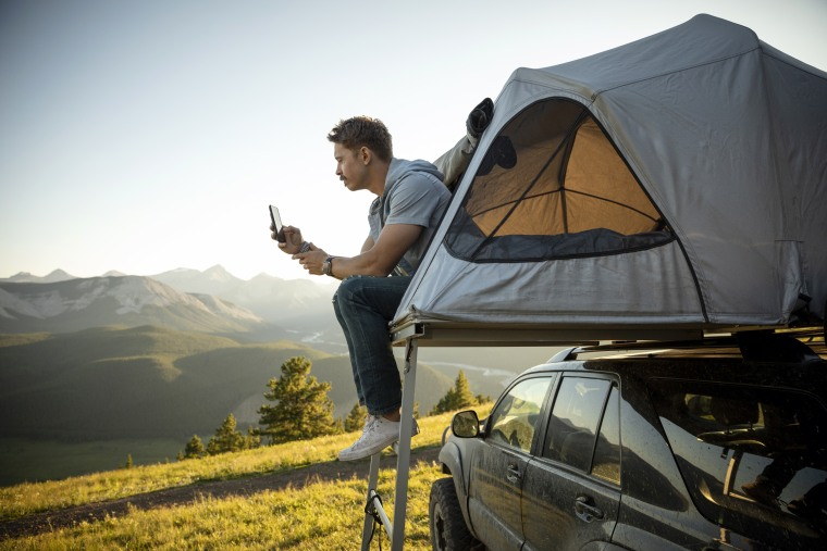 Serene man camping, relaxing at SUV rooftop tent in sunny, idyllic field, Alberta, Canada