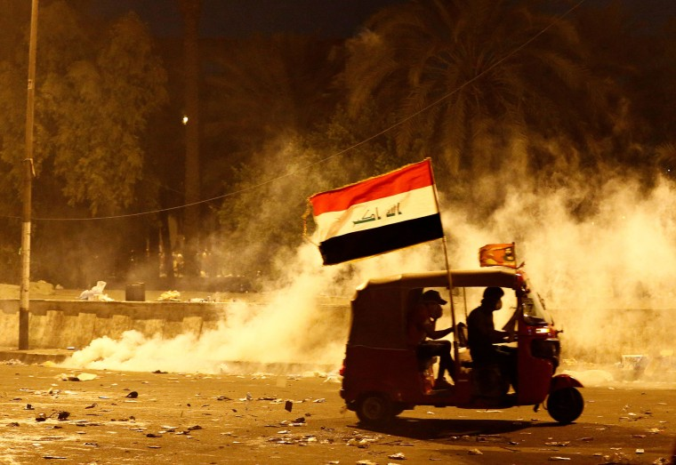 Image: A tuk-tuk drives away from tear gas fired by Iraqi security forces during a protest over corruption, lack of jobs, and poor services, in Baghdad
