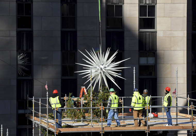 Workers secure the 2019 Swarovski Star to the top of the 77-foot Rockefeller Center Christmas tree on Nov. 13, 2019, in New York.
