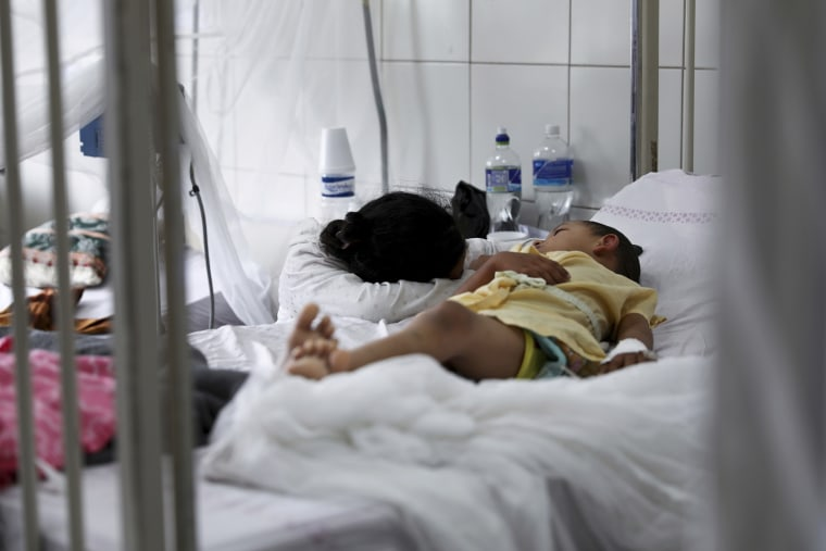 A relative embraces a young patient receiving treatment for dengue at the University School Hospital in Tegucigalpa, Honduras on Aug. 20, 2019.