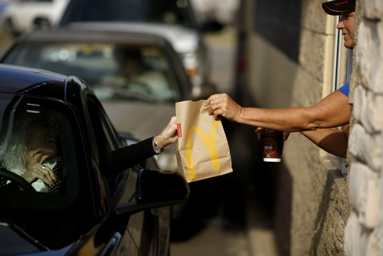 Image: A worker hands a bag of food to a customer at a McDonald's drive-thru window in Tenn., in 2017.