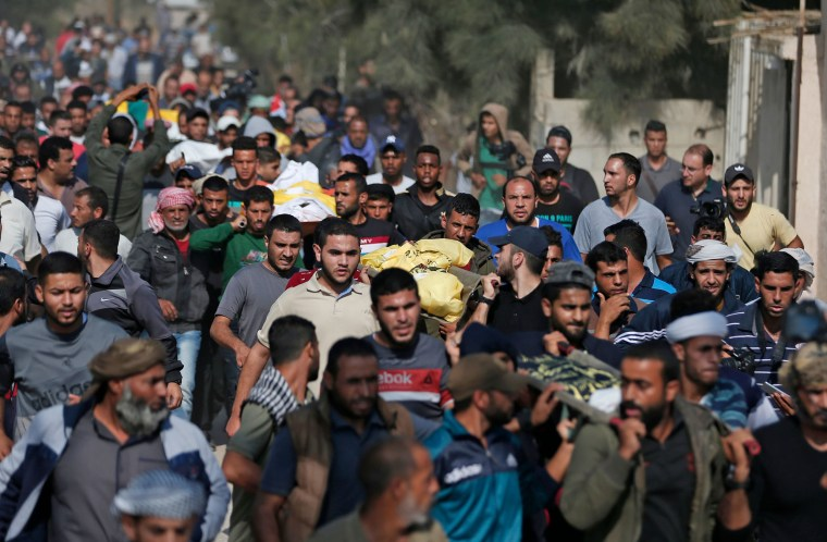 Image: Palestinians attend the funeral procession of members of the same family who were killed overnight in an Israeli airstrike