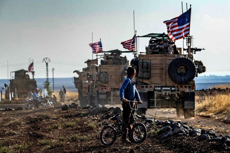 Image: A Syrian boy looks at a U.S. convoy patrolling near the Turkish border on Oct. 31, 2019.
