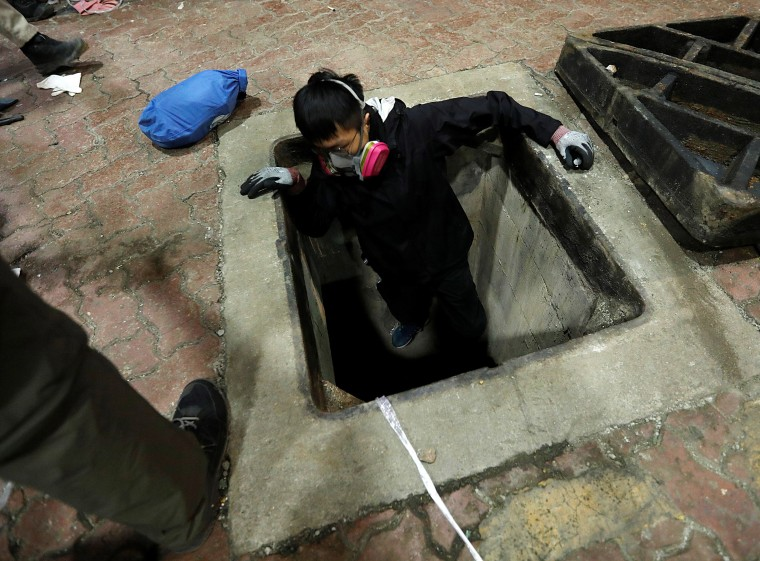 Image: A protester tries to escape through a sewage tunnel inside the Hong Kong Polytechnic University campus during protests in Hong Kong, China