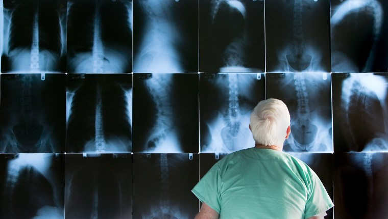 Senior doctor looking at x-rays, rear view