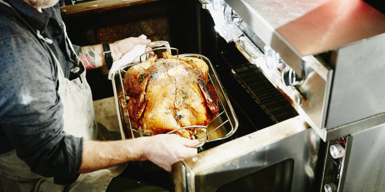 Man pulling cooked turkey out of oven