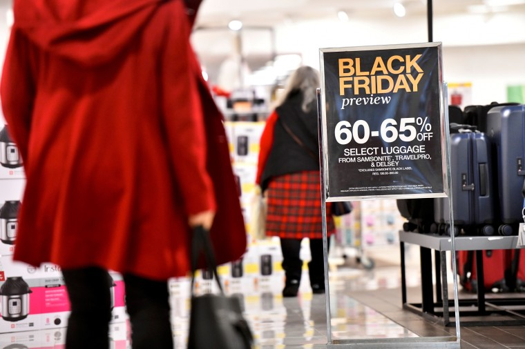"Image: Shoppers walk past a placard that states ""Black Friday preview"" at a Macy's store as holiday shopping accelerates at the King of Prussia Mall"