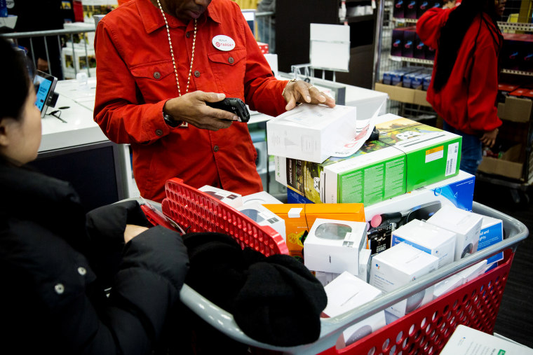 Image: An employee scans merchandise at a Target store in Westbury, N.Y., on Nov. 22, 2018.