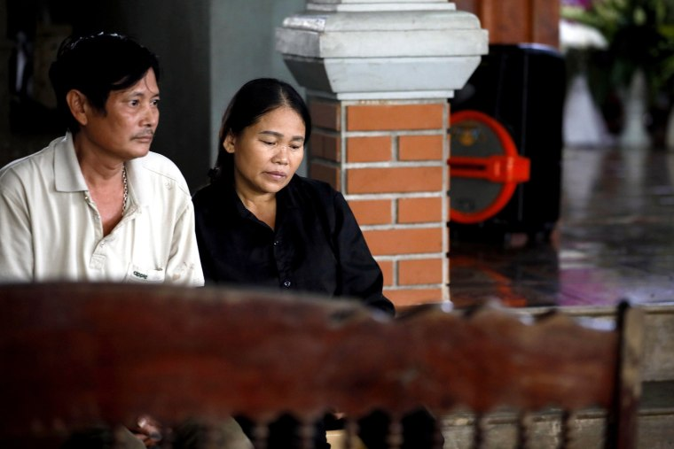 Image: Hoang Lanh, left, and Hoang Thi Ai, parents of Hoang Van Tiep, one of the 39 truck victims in England, waits for the arrival of their son's coffin at his home in a village in the Dien Chau district, Nghe An province, Vietnam