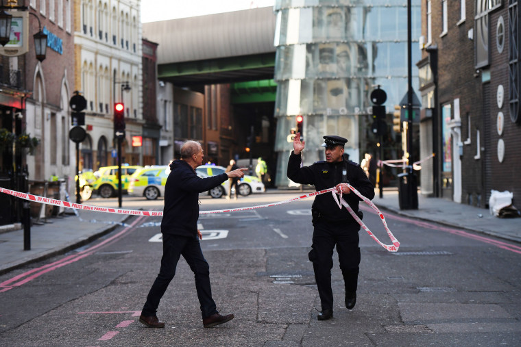 Image: Members of the public are held behind a police cordon near London Bridge train station