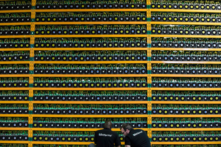 Image: Two technicians inspect bitcon mining at Bitfarms in Saint Hyacinthe, Quebec