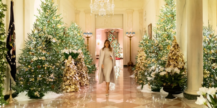 "First lady Melania Trump walks the Cross Hall inside the White House, now adorned in Christmas decor in a theme she's called ""The Spirit of America."""