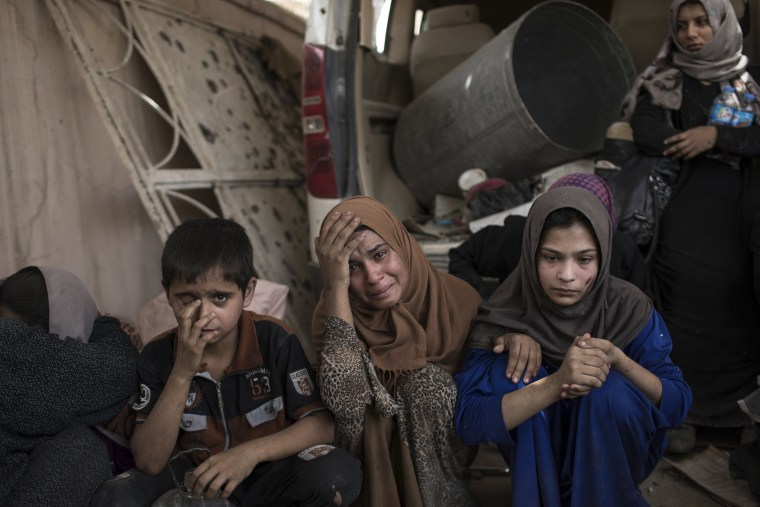 Image: Fleeing Iraqi civilians sit inside a house as they wait to be taken out of the Old City