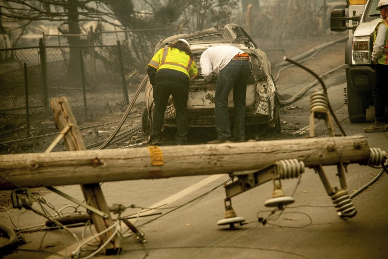 Image: Eric England, right, searches through a friend's car near a downed utility pole after the Camp fire blazed through California on Nov. 10, 2018.