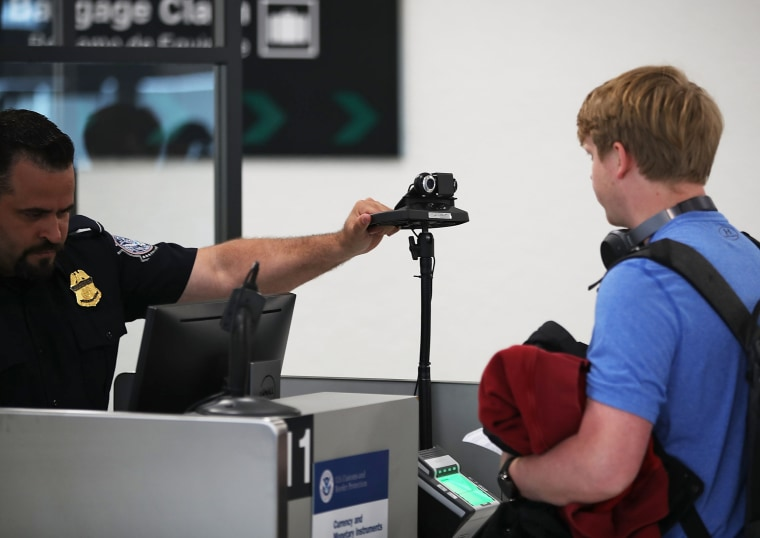 A U.S. Customs and Border Protection officer instructs an international traveler to look into a camera as he uses facial recognition technology to screen a traveler entering the United States at Miami International Airport in 2018.