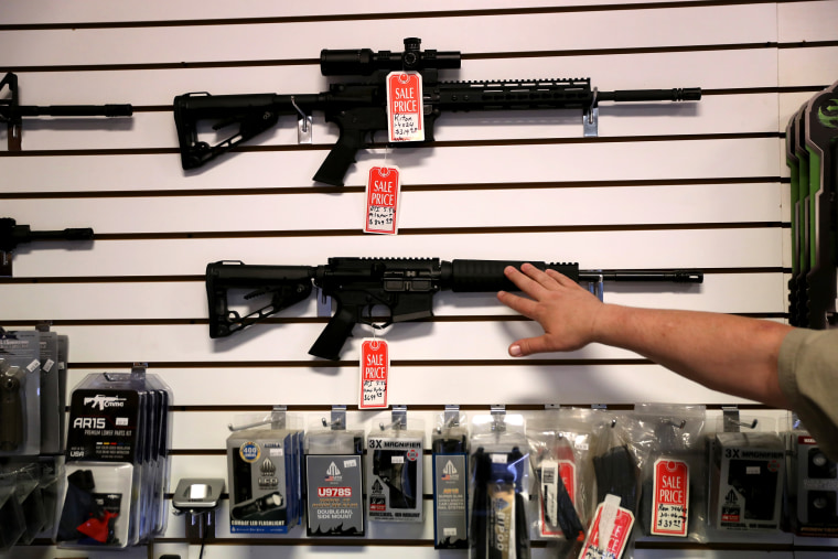 Image: A gun shop owner puts an AR-15 on display in Benson, Ariz., on Sept. 29, 2016.