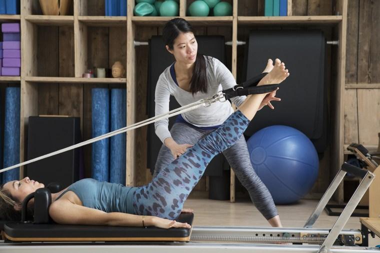 Image: Pilates teacher assists student using reformer for leg exercises