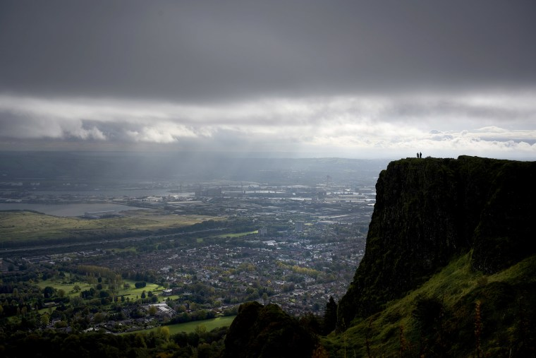 Image: Hill walkers look over north Belfast from Cave Hill.