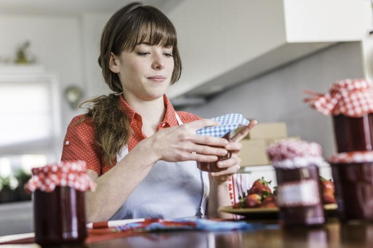 Image: Woman packing homemade strawberry jam