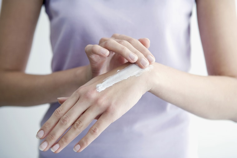 Image: Woman applying cream to hands, close-up