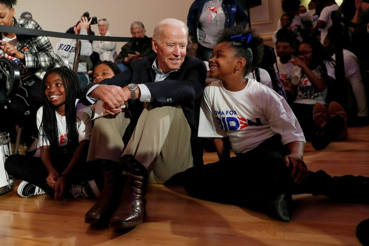 Image: Democratic 2020 presidential candidate and former Vice President Joe Biden sits with kids from the Union Baptist Crusaders drill team during an event at the Brown Derby Ballroom in Waterloo, Iowa